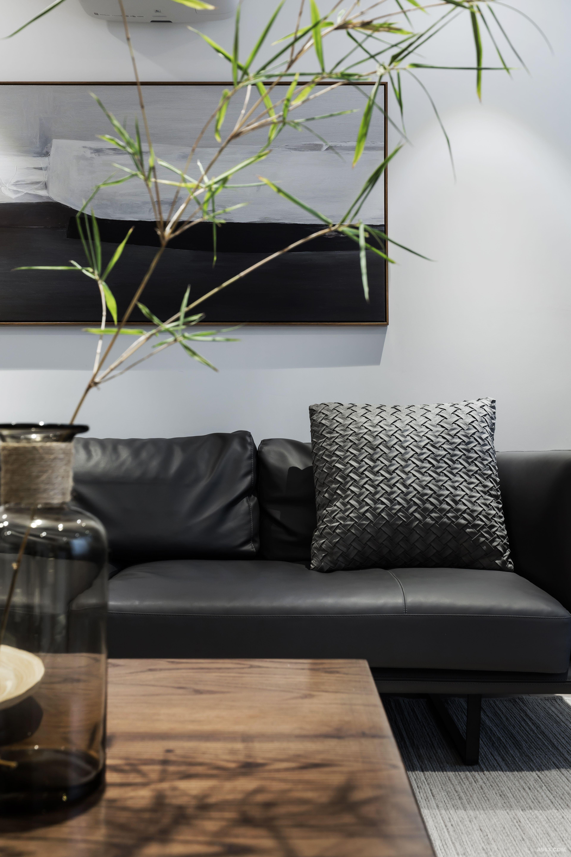 黑色皮质沙发,原木色茶几与原木色边框的挂画.有质感.